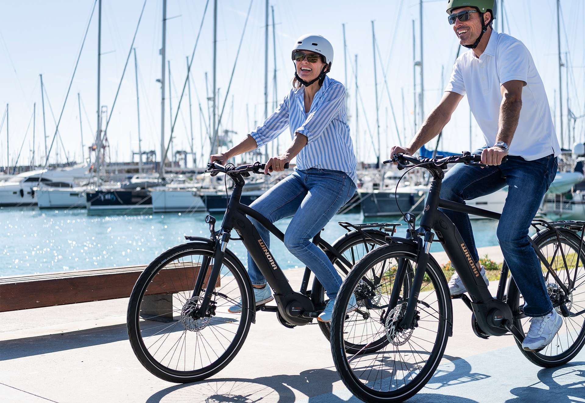 Couple riding on Winora electric bikes through a harbour