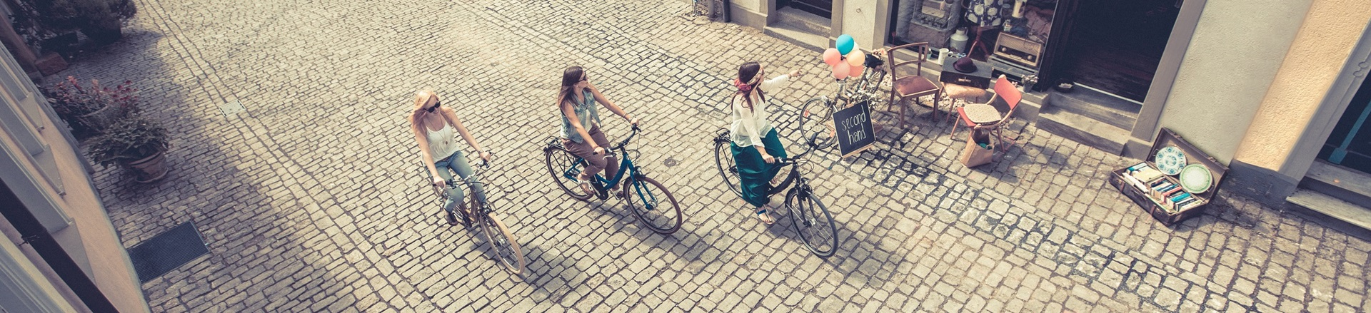Three women cycling through the city on their Winora Ladies City Bikes