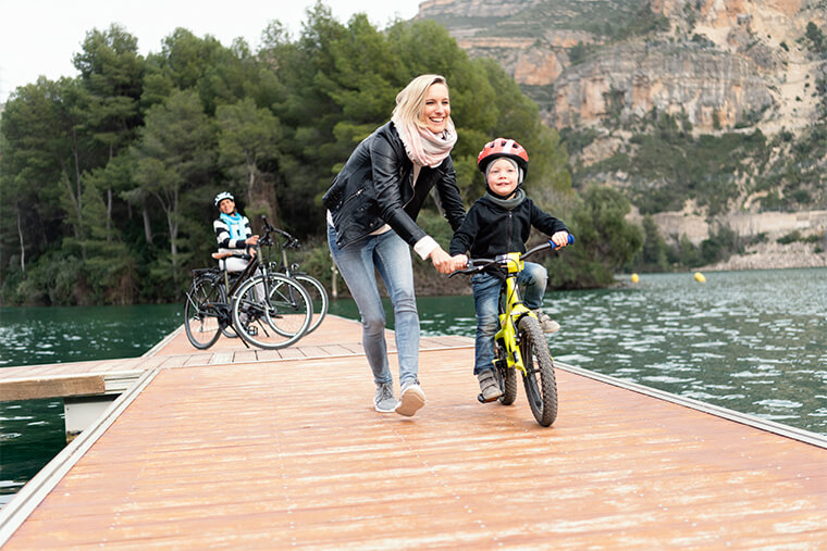 Mother helping her son to cycle on a Winora kids' bike