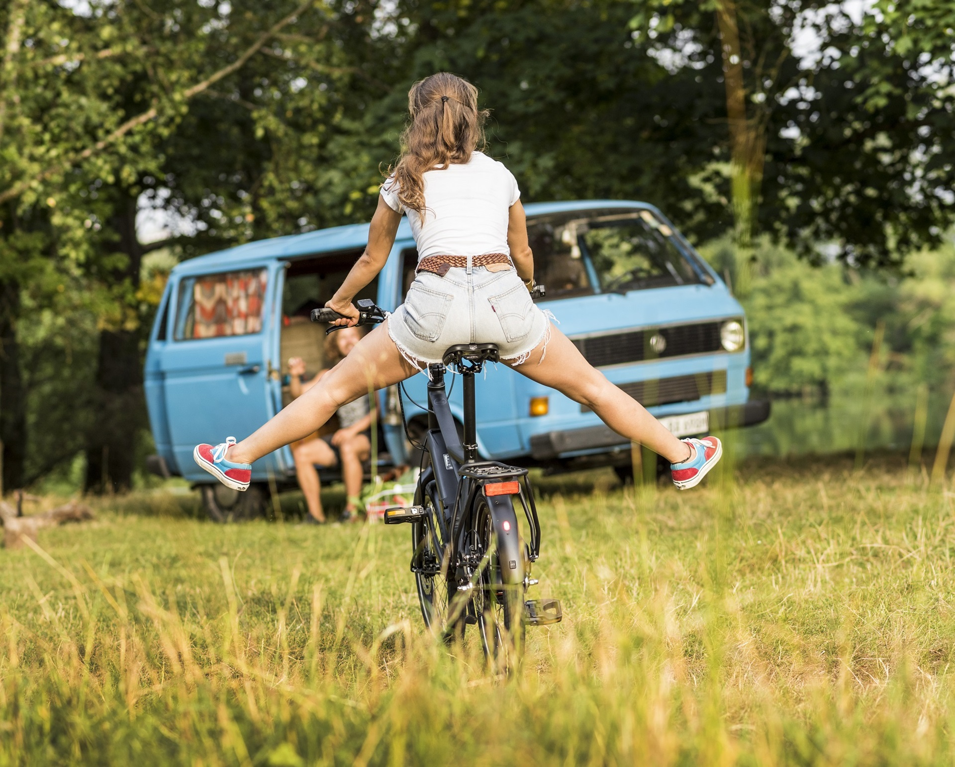 girl rides winora bike in grass field