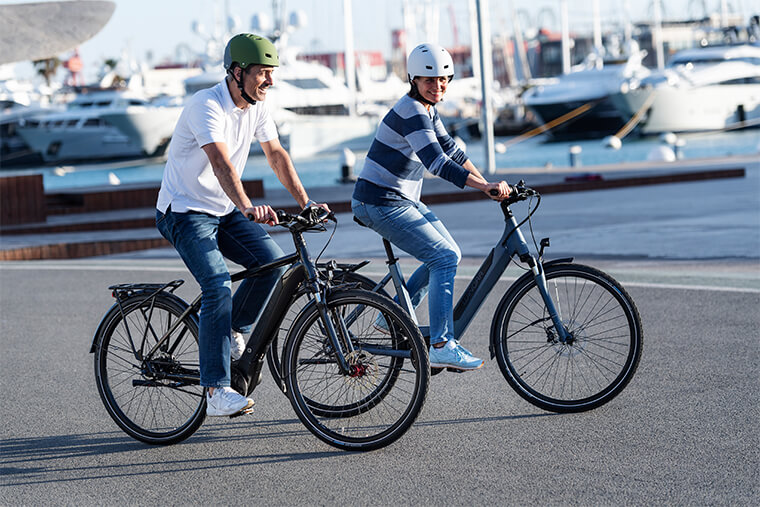 Couple riding through a harbour on Winora e-bikes